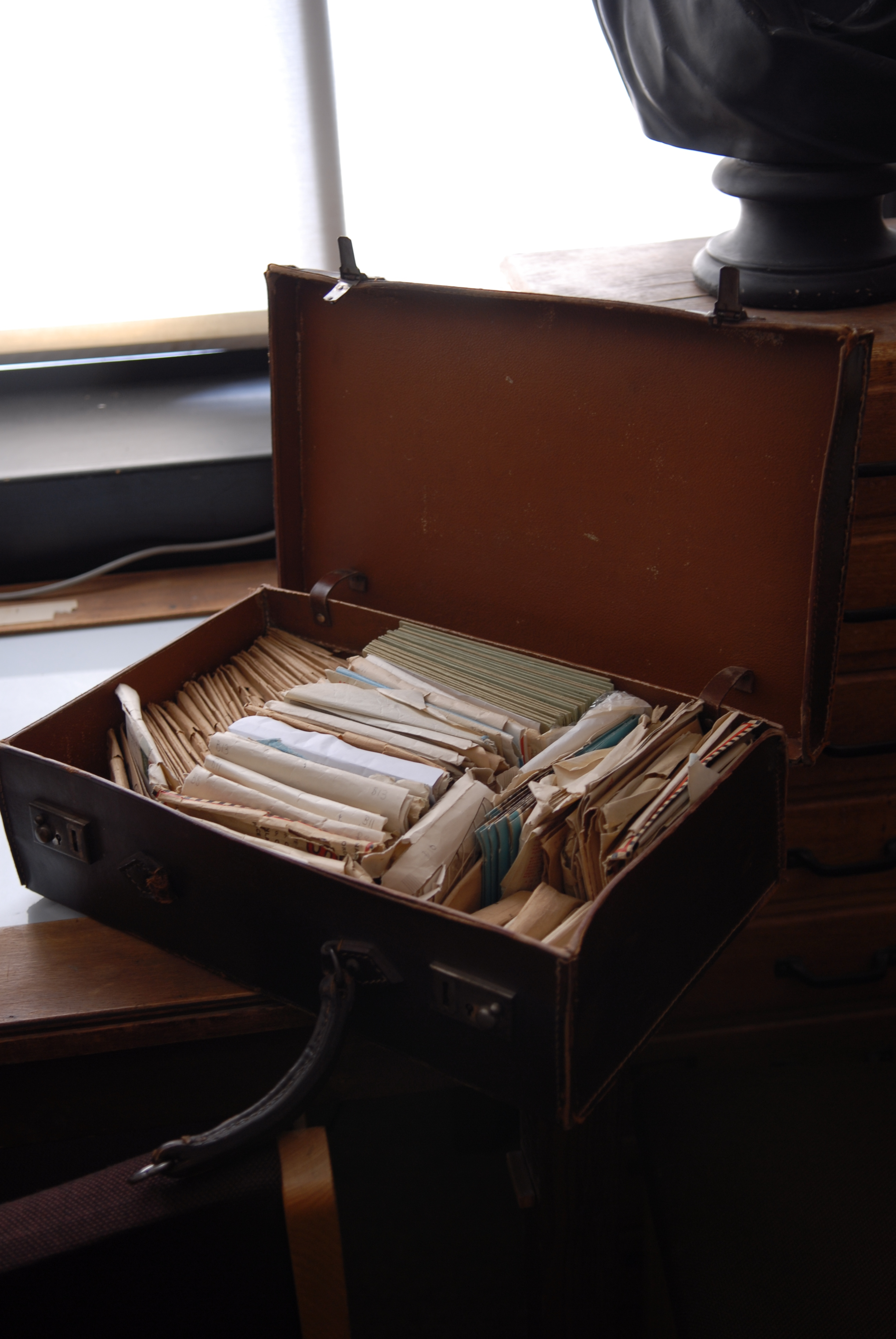 an open brown leather suitcase filled with envelopes