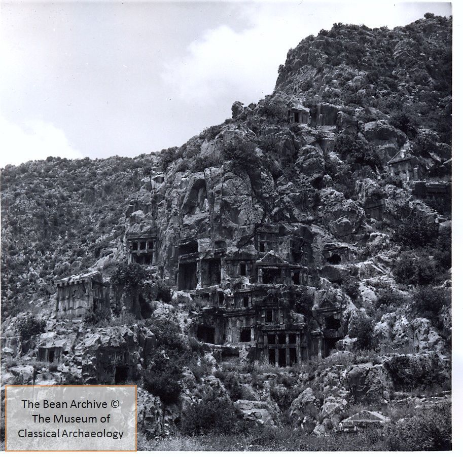 black and white photograph of a hillside with rock-cut tombs