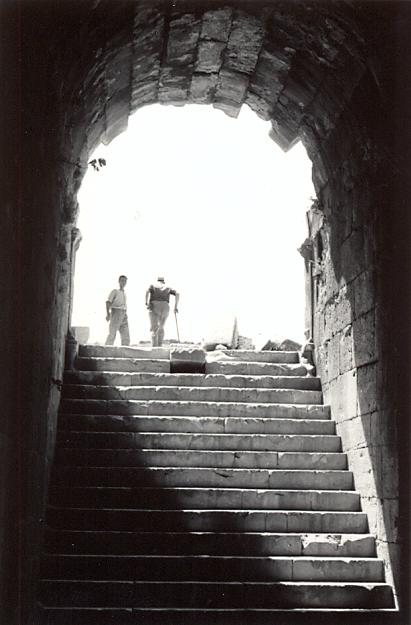 black and white photograph of an steps leading up to an archway, with two men seen from behind