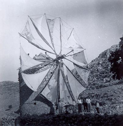 black and white photo of a group of men in front of a windmill