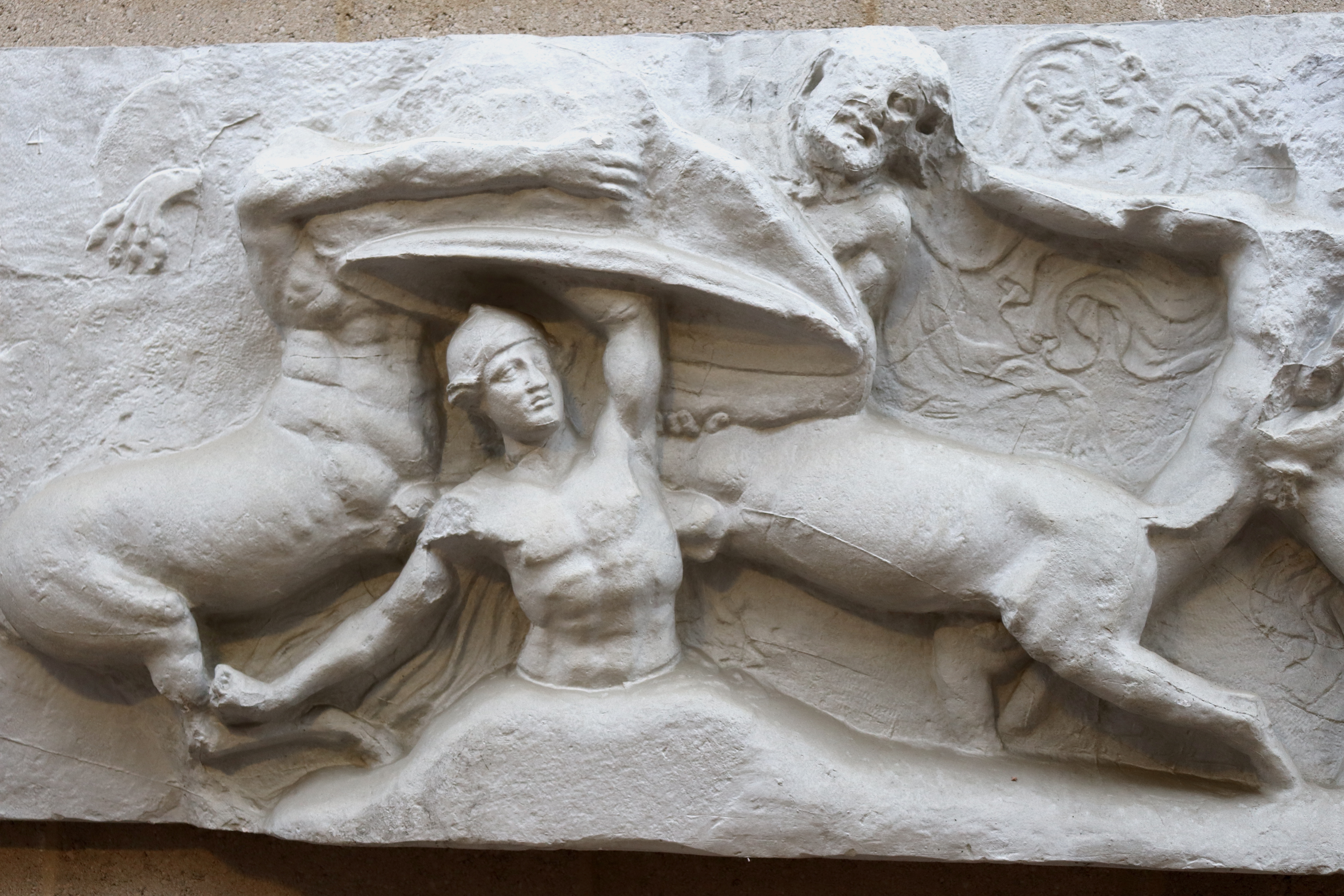 scene from Bassai frieze with Caineus being beaten into ground by centaurs