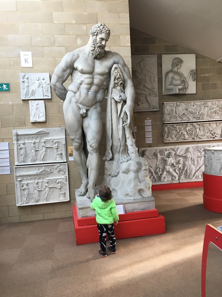 a little boy in a bright green coat stands in front of a huge sculpture of a naked bearded man
