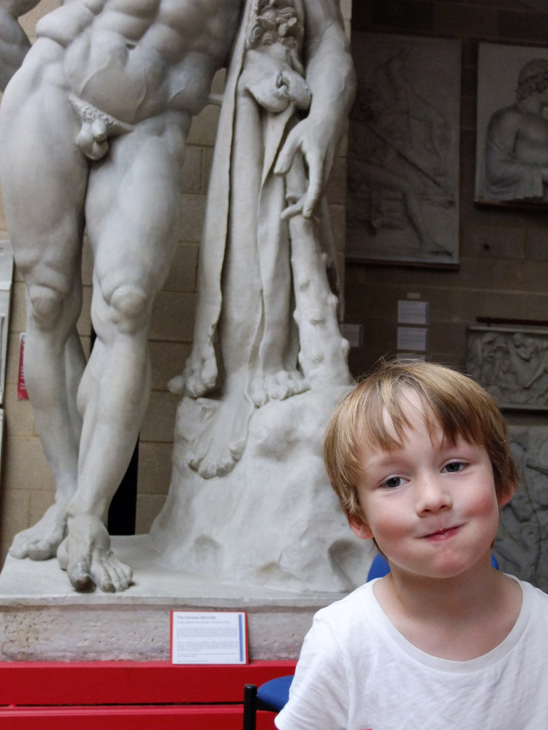 a little boy stands in front of the legs of a huge statue of a naked man