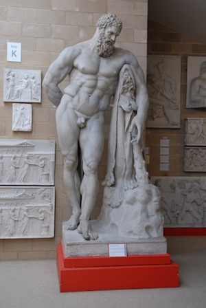 sculpture of naked Hercules, leaning on club with animal skin
