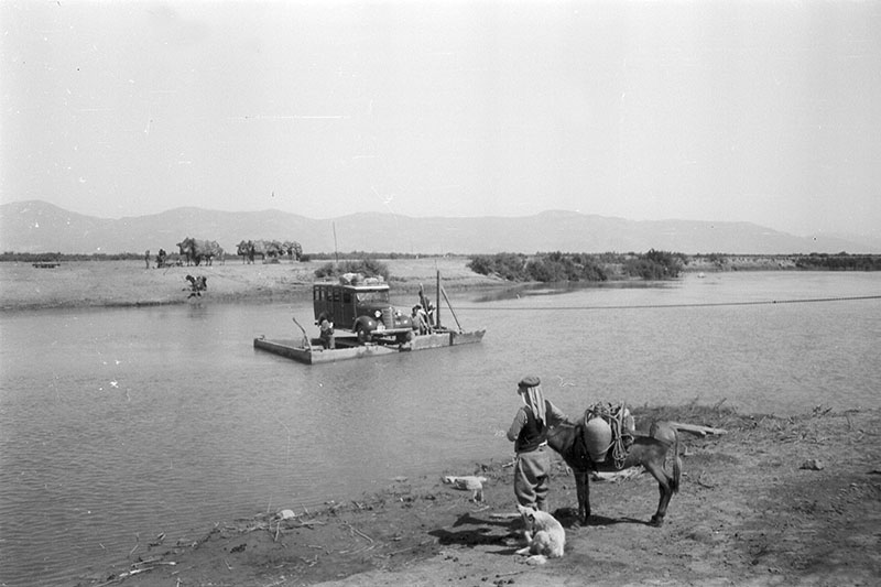 black and white photograph of a raft on a river and a man and donkey on the shore