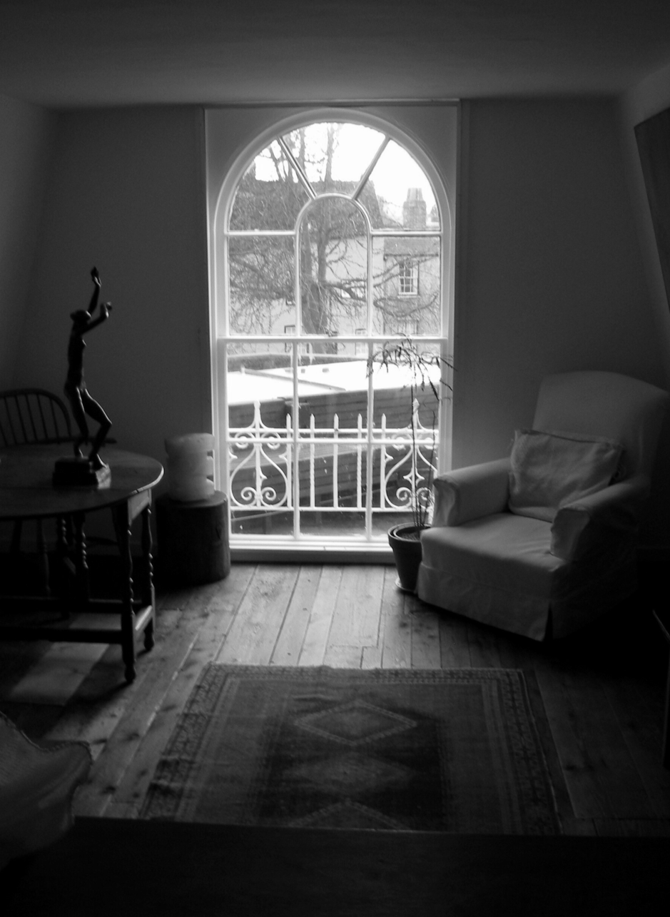 black and white image of a window with an armchair and a dancing figure on a table