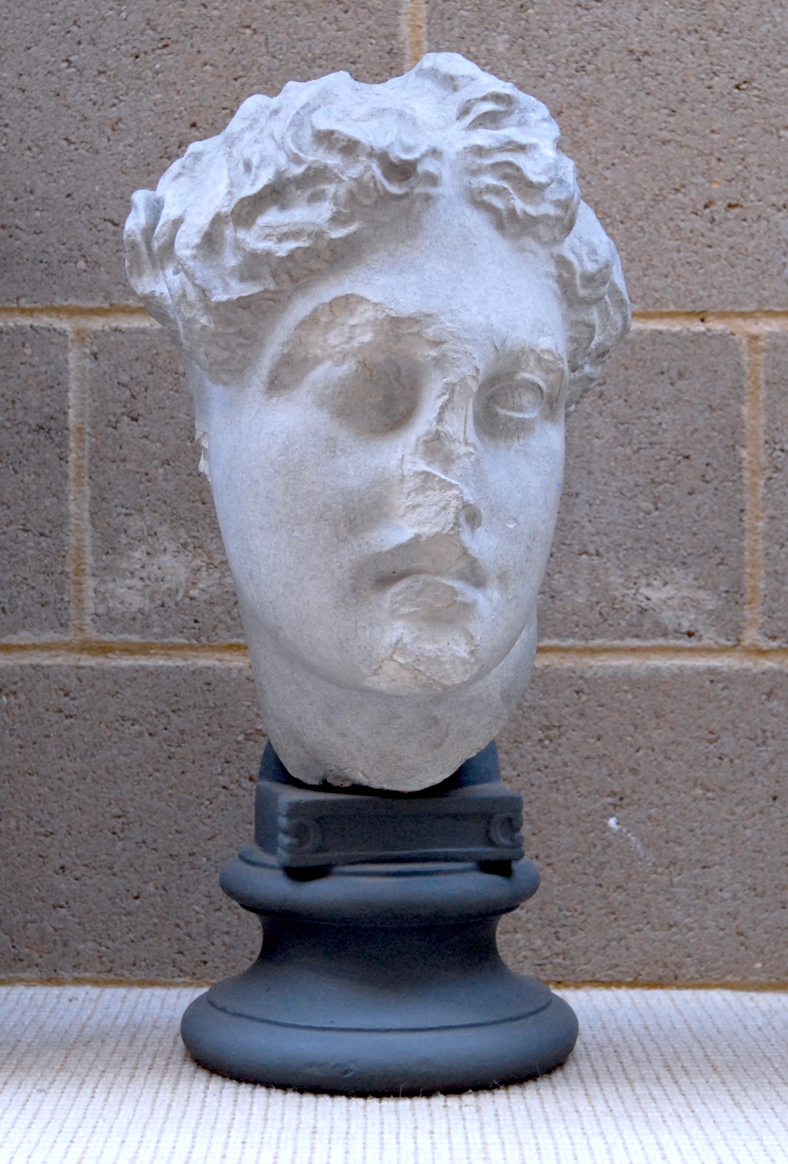 sculpted head of apollo, head bent to one side, with hair in little knots on top of head