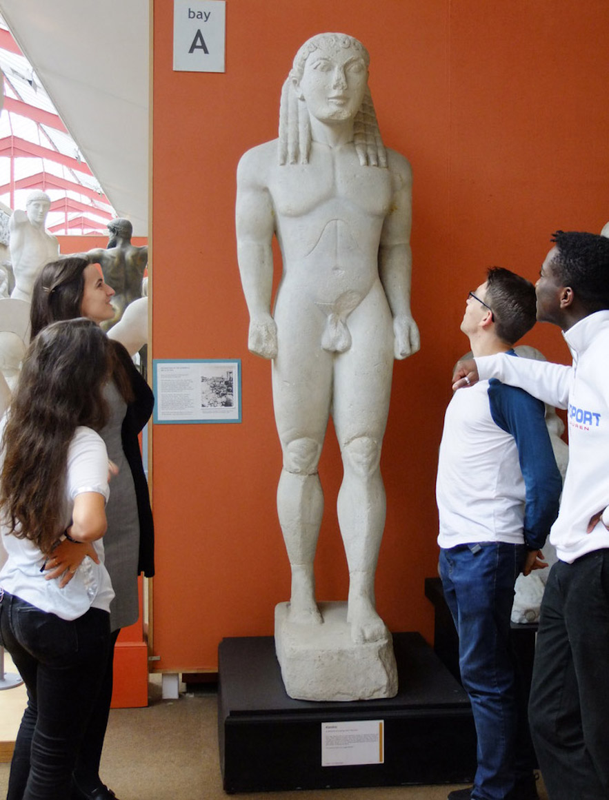 a group of men and women look at a Greek sculpture of naked young man with long hair