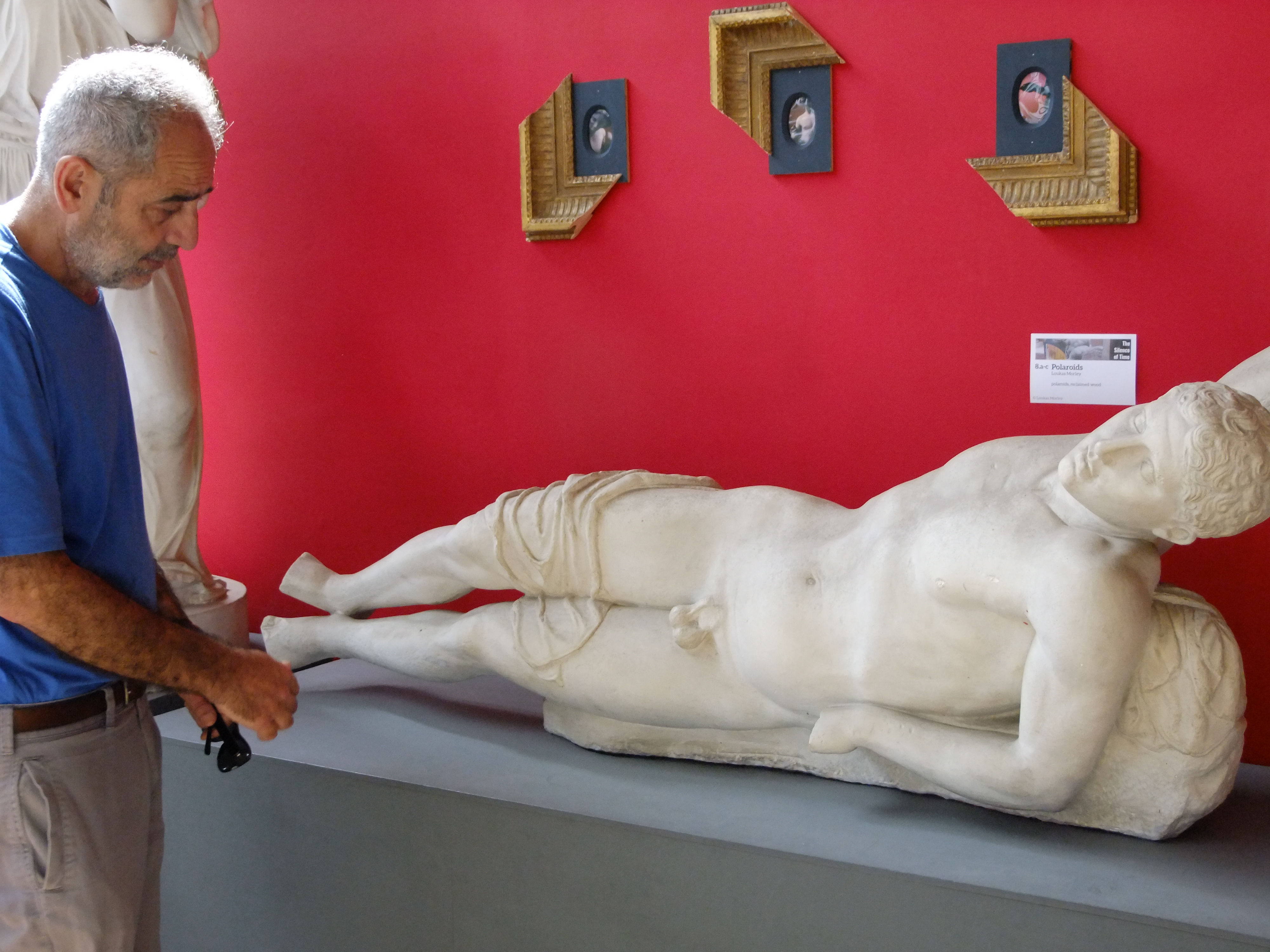 A Syrian man stands mournfully looking at a sculpture of reclining young man