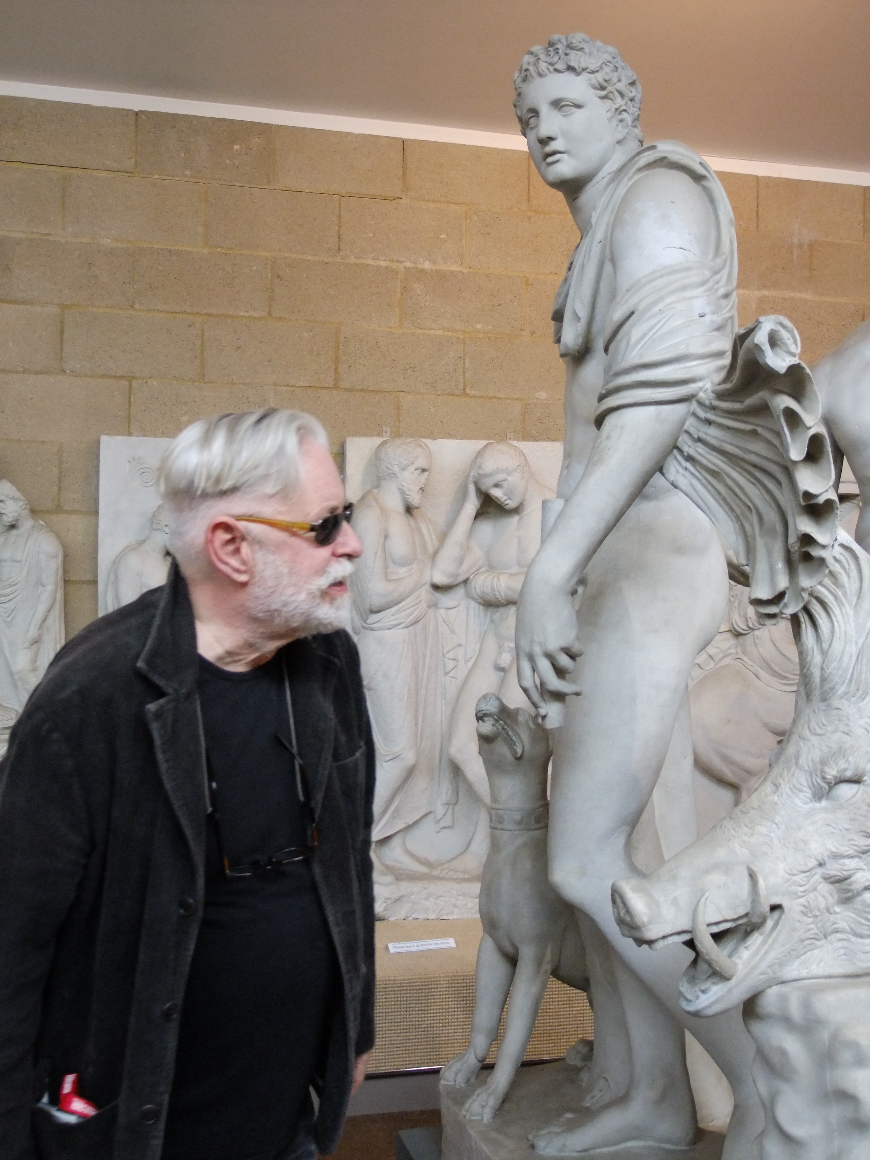 a man in sunglasses looks at a sculpted young man with boar's head and dog
