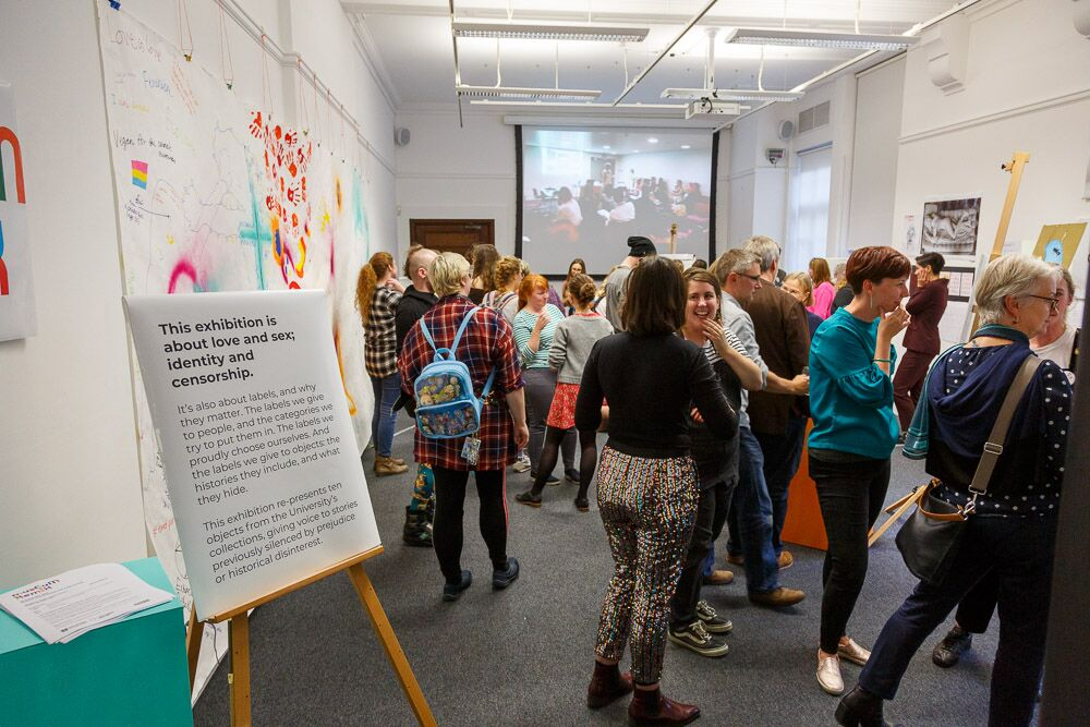 lots of people at a party for the Museum Remix display, with a large information panel in foreground