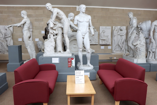 two red sofas with arm-rests next to a low table, amongst statues