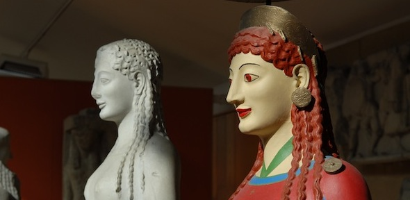 sculpted head of a woman with red hair and a red dress, with unpainted version in background