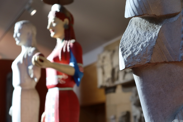 view of unpainted and painted Peplos Kore, out of focus in background