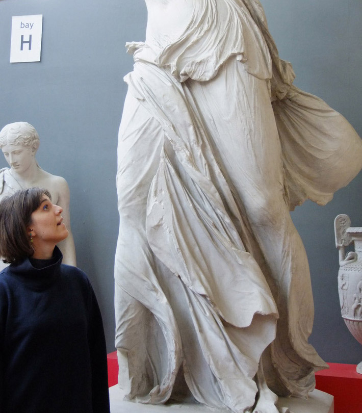 a young woman with short dark hair looks up toward a sculpted female figure