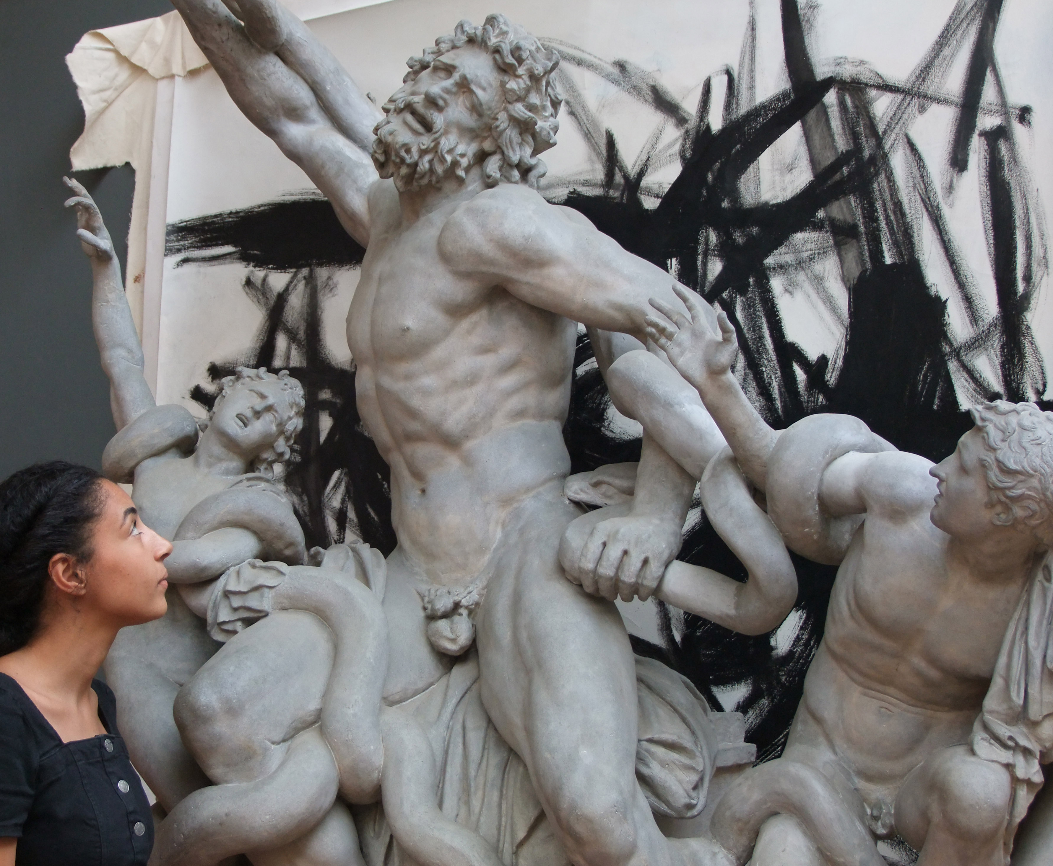 a young woman of mixed heritage looks at a sculpture of a father and two sons fighting snakes