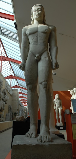 statue of naked young man with hands clenched at sides and one foot in front of other