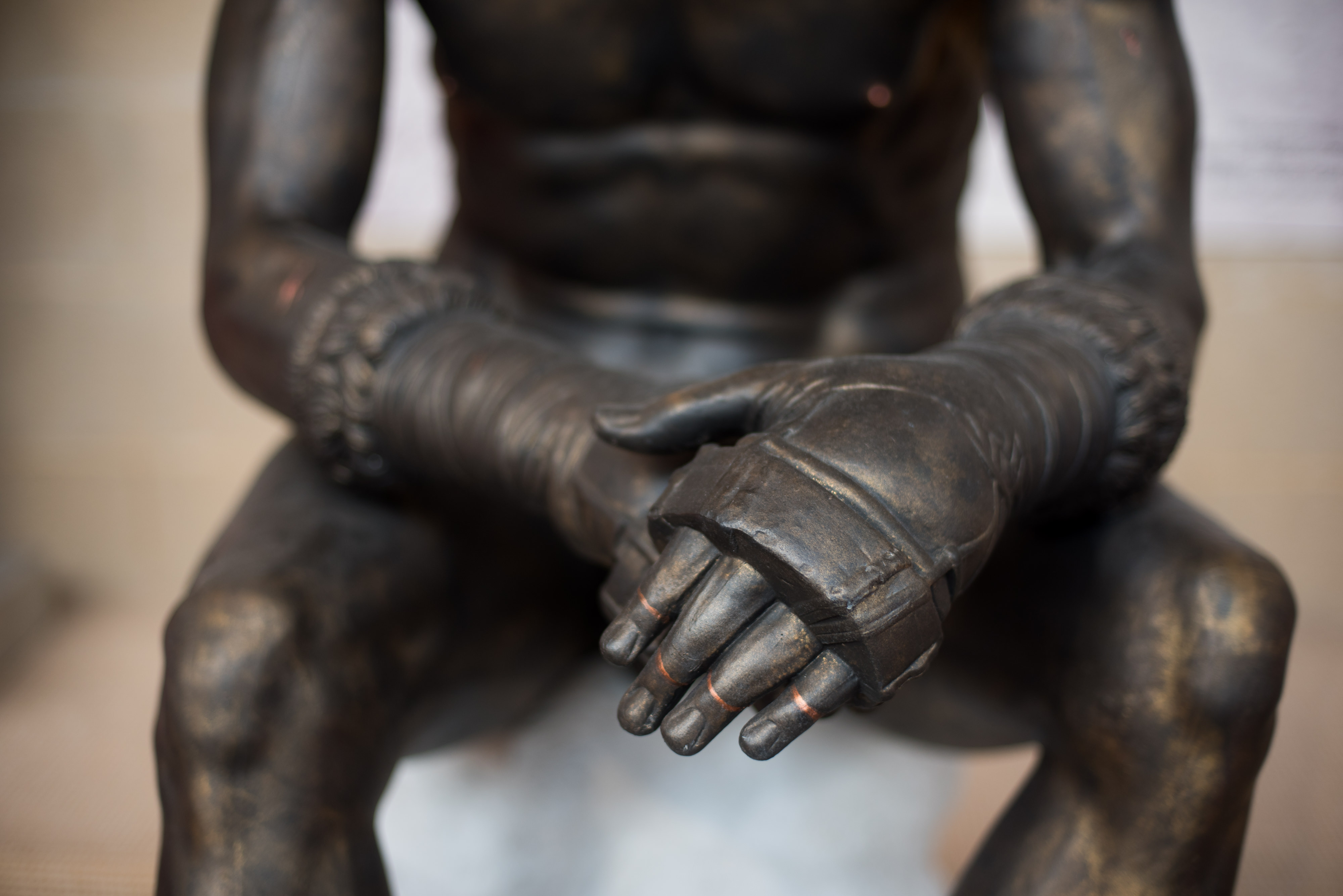 close up of Boxer's hands wearing fur-lined boxing gloves with metal knuckle guards