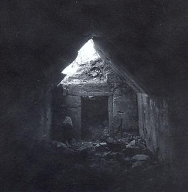 black and white photo of a little local boy seated in a dark tomb interior