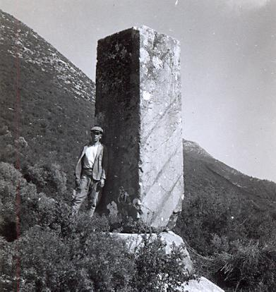 black and white photo of a local young man next to a standing stone