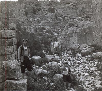 black and white photo of three local Turkish men and a little boy standing in ruins