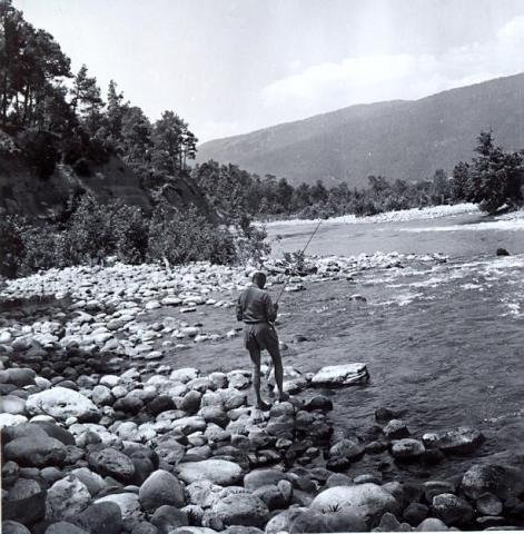 black and white photo of a man fishing, from behind