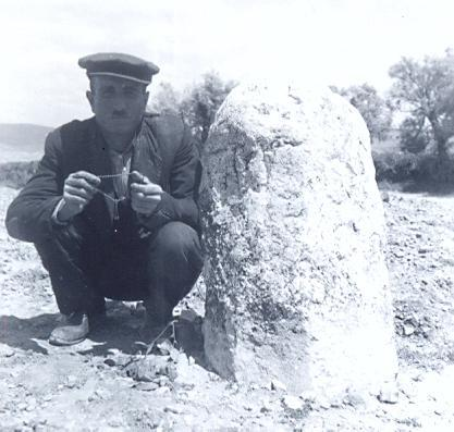 black and white photo of a local Turkish man kneeling nex tot a standing stone