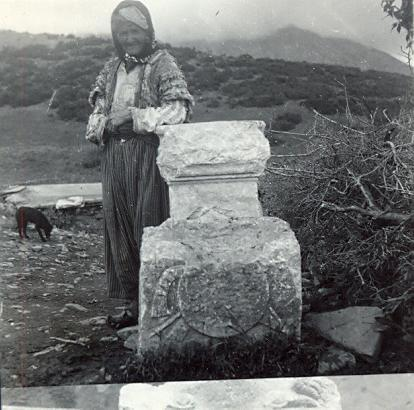 black and white photo of a local Turkish woman in a headscarf standing next to a standing stone