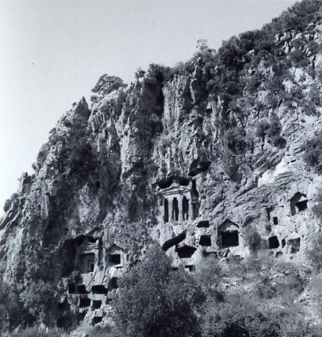black and white photo of rock-cut tombs/apertures in a hillside