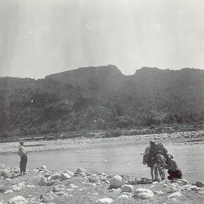 black and white photographoof a donkey and two men next to a body of water
