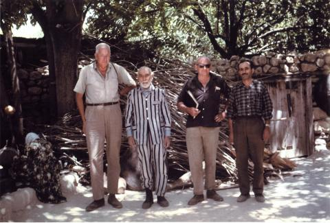 colour photo of four men in front of trees and a stone wall