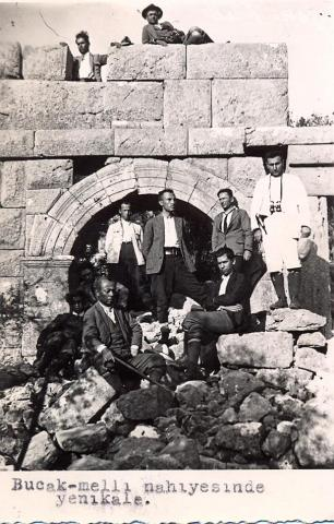 black and white photo of a group of local Turkish men standing in front and lying on an arch in a ruined wall