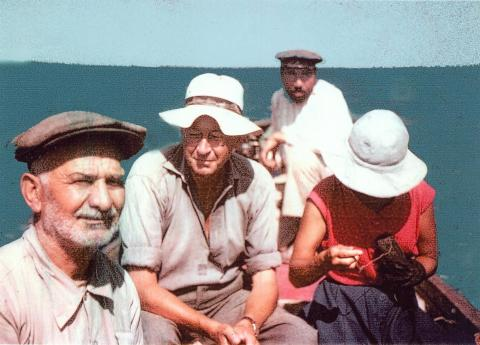 Colour photograph of George and Jane on a boat with two locals