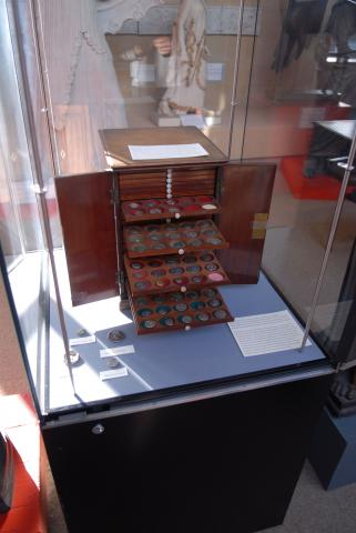 a display cabinet with an open wooden box of drawers with coins