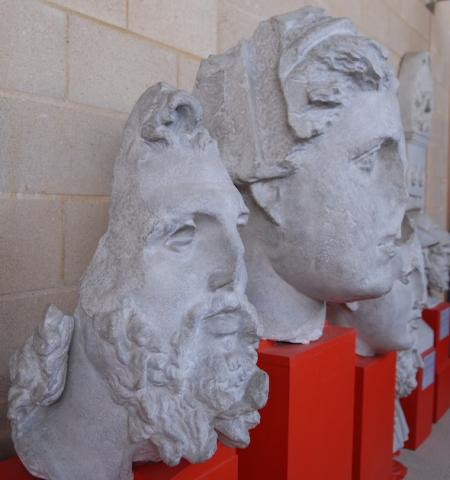 a sculpted head of a bearded man nex to the head of woman, with other heads behind