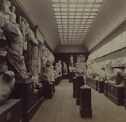 black and white photograph of museum interior with plaster casts