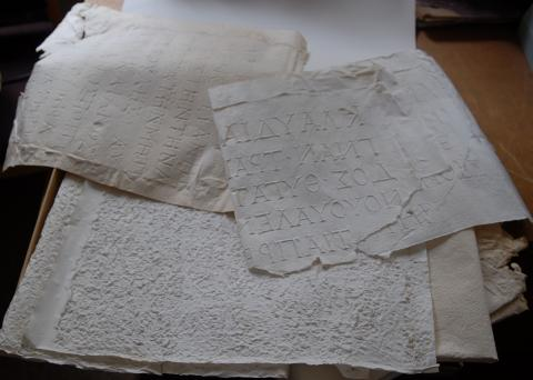 colour photograph of paper imprints of inscriptions (squeezes) on a table