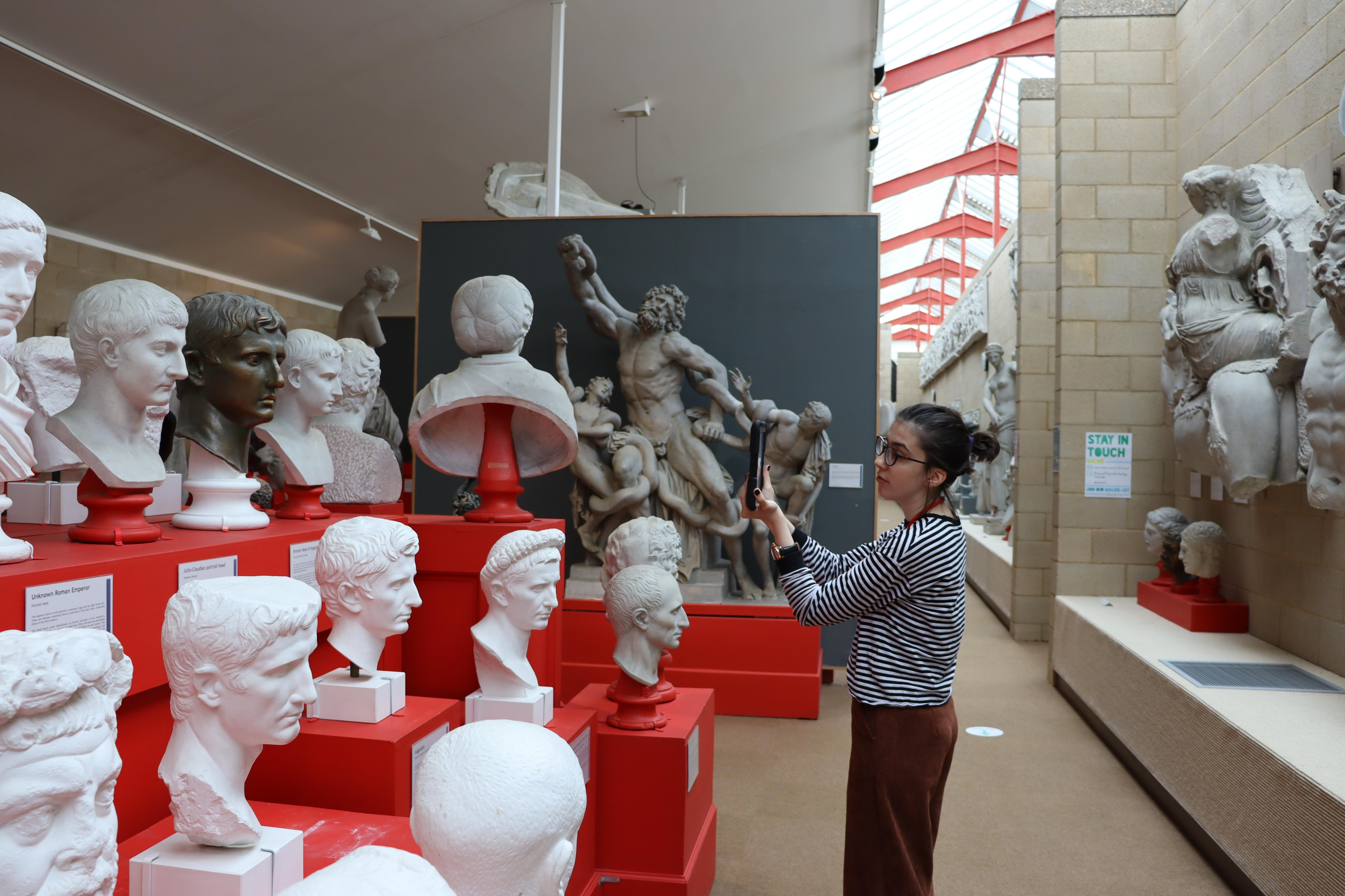 Justyna holding an iPad. busts of roman emperors on the left. Laocoon in the background.