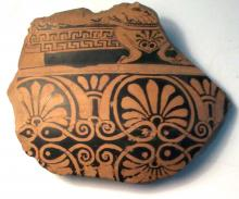 broken piece of Greek pottery, with black patterns on red background' width=