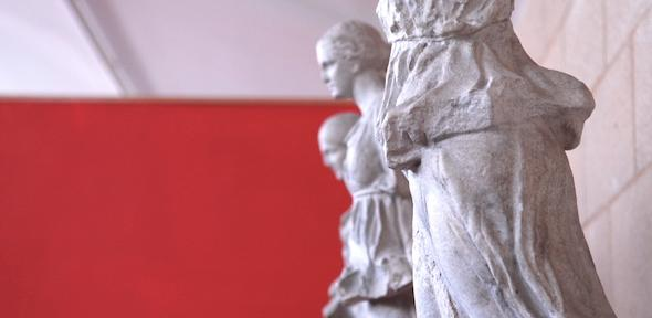 three sculpted women against a red background