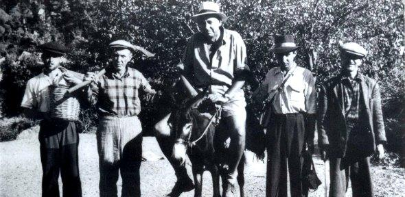black and white photograph of George on a donkey with four local Turkish guides