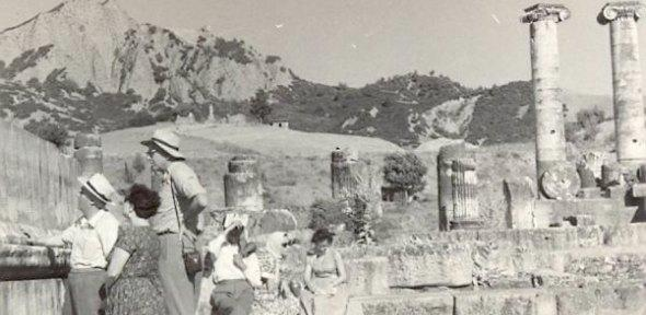 black and white photo of a group of men and women looking at a ruined temple