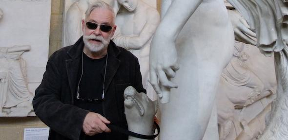 A man with grey hair and sunglasses puts a lead on a sculpted dog