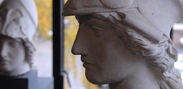 sculpted head of Athena in helmet, with leafy background