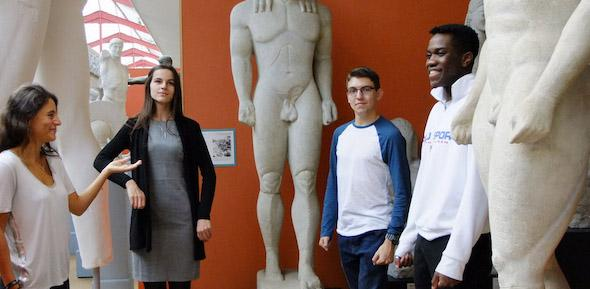 four students of different ages stand around archaic statues against an orange wall