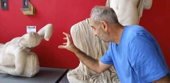 Issam Kourbaj reaches out to one of the dying Niobid statues, against a red wall