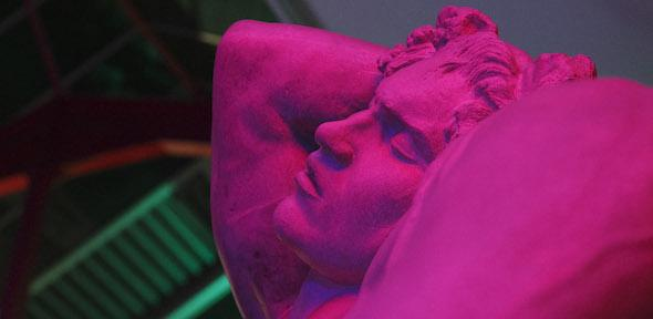 close up on face of reclining Barberini Faun, in pink light