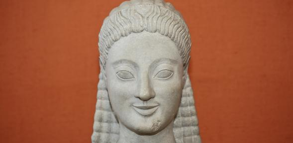 head of an archaic kouros, against an orange background