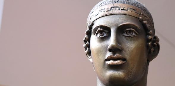 Bronze face of Delphi chariotteer with painted eyes and copper lips
