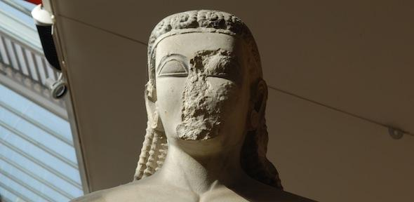 head of sounion kouros with damage to face, large almond-shaped eyes, and braided hairstyle
